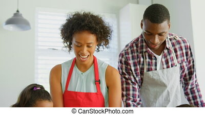 Front view of black family using cookie cutter in kitchen at home. Black family preparing food in kitchen 4k
