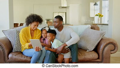 Front view of black family using digital tablet in living room at home 4k