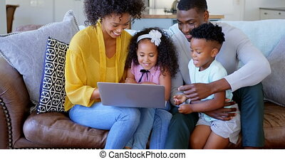 Front view of black family using laptop in living room at home 4k