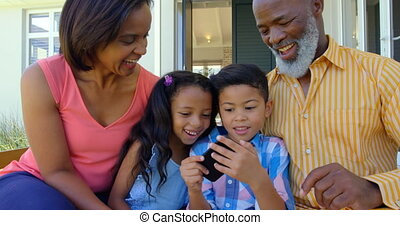 Front view of black family using mobile phone in a comfortable home 4k