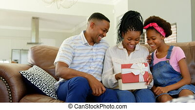 Front view of black father and daughter giving birthday gift to woman in living room at home 4k