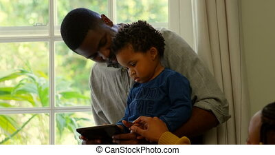 Front view of black father and son using digital and sitting...