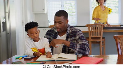 Front view of black father helping his son with homework at comfortable home. Mother cooking food in the background 4k