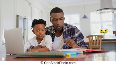 Front view of black father helping his son with homework at comfortable home 4k