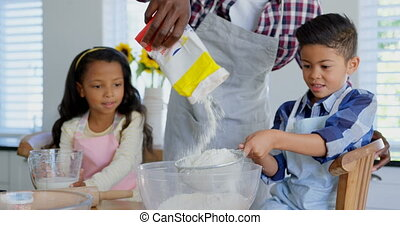 Front view of black father with his children preparing food in kitchen 4k