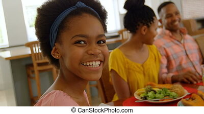 Front view of black girl having food with her family at dining table in a comfortable home 4k