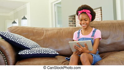 Front view of black girl sitting on the couch and using digital tablet in a comfortable home 4k