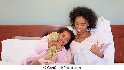 Front view of black mother and daughter reading story book in a comfortable home 4k
