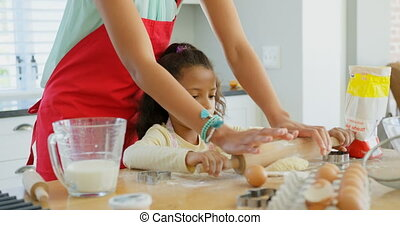 Front view of black mother and daughter rolling dough with rolling pin at home 4k
