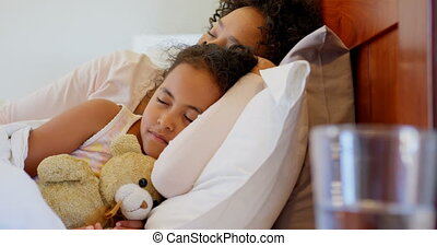 Front view of black mother and daughter sleeping in bedroom at home 4k