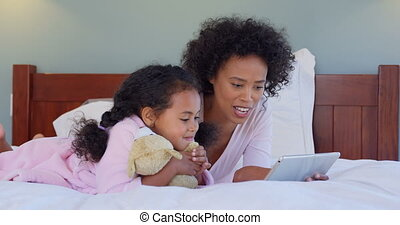 Front view of black mother and daughter using digital tablet at comfortable home 4k