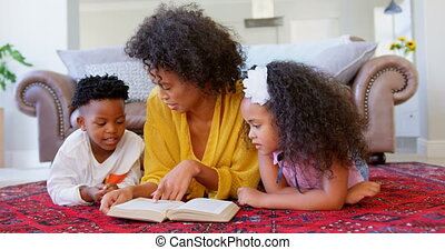 Front view of black mother with her children reading a book in a comfortable home 4k
