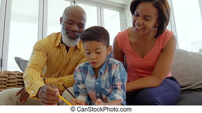 Front view of black parents helping son with homework in a comfortable home 4k