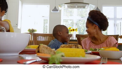 Front view of black sibling having food at dining table in a comfortable home 4k