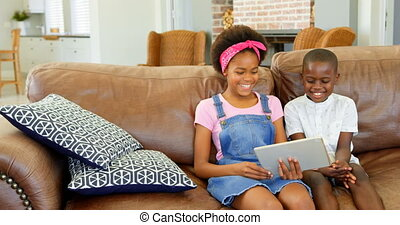 Front view of black siblings sitting on the couch and using digital tablet in a comfortable home 4k