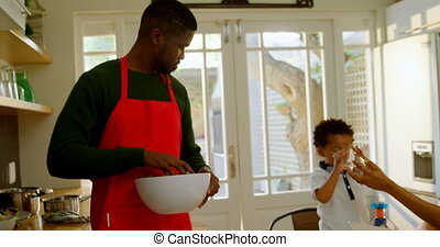 Front view of black young father washing vegetable in kitchen of comfortable home 4k