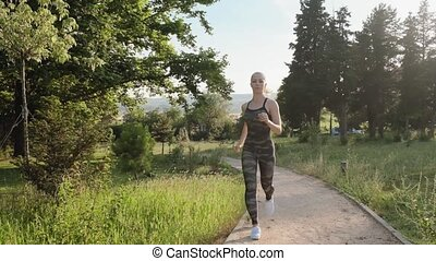 Front view of blond woman running in the park in khaki...