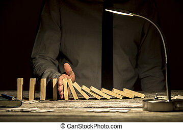 Front view of businessman stopping falling dominos with his hand