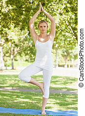Front view of calm woman in tree yoga pose on an exercise mat