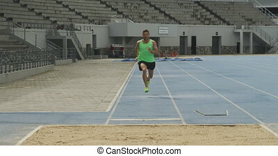 Front view of caucasian athlete doing long jump - Front view...