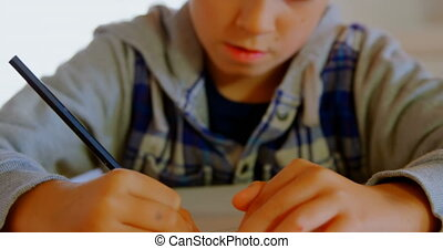Front view of Caucasian boy doing his homework at dining table in a comfortable home 4k