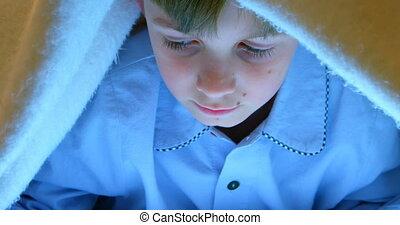 Front view of Caucasian boy under blanket in bedroom at comfortable home 4k