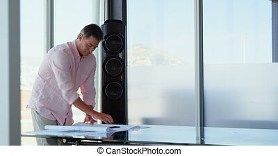 Front view of Caucasian Businessman looking at blueprint in a modern office 4k