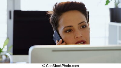 Front view of Caucasian Businesswoman talking on mobile phone at desk in a modern office 4k
