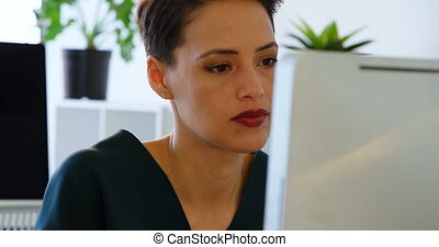 Front view of Caucasian Businesswoman working on computer at desk in a modern office 4k