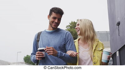 Front view of Caucasian couple on the go drinking a takeaway coffee
