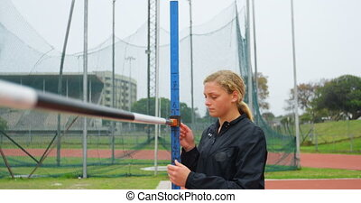 Front view of Caucasian female athlete checking high jump bar at sports venue. She is walking at sports venue 4k