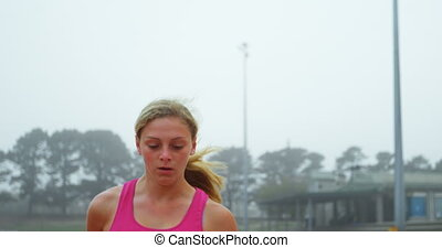 Front view of Caucasian female athlete exercising on running track at sports venue. She is standing on a running track 4k