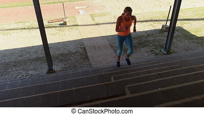 Front view of Caucasian female athlete exercising on steps at sports venue. She is fit and healthy 4k