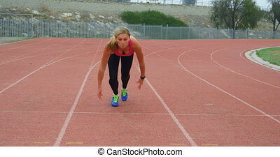 Front view of Caucasian female athlete running at sports venue. She is fit and healthy 4k