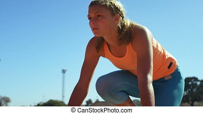 Front view of Caucasian female athlete taking starting ...