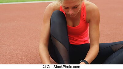 Front view of Caucasian female athlete wearing shoes on running track at sports venue. She is sitting on a running track 4k