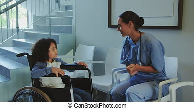 Front view of Caucasian female doctor interacting with disabled boy in the corridor at hospital 4k