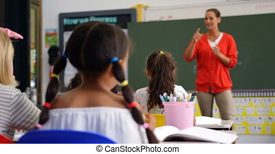 Front view of Caucasian female teacher teaching schoolkids in the classroom 4k