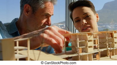 Front view of Caucasian male and female architects discussing over building model in office 4k