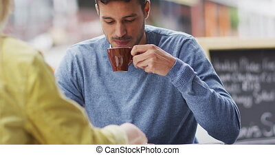 Front view of Caucasian man drinking coffee on a terrace - ...