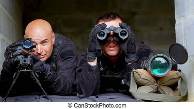 Front view of caucasian military soldiers looking through binoculars and riflescope at training. They are lying on ground 4k
