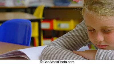 Front view of Caucasian schoolgirl sleeping on desk in classroom at school 4k
