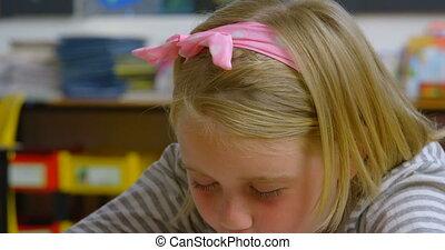 Front view of Caucasian schoolgirl sleeping on desk in classroom at school. She is snoring 4k