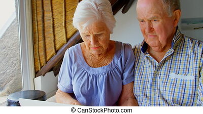 Front view of Caucasian senior couple using laptop at comfortable home 4k