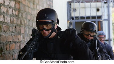 Front view of caucasian soldiers conduct military exercise at military base. They are standing against the wall 4k