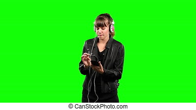 Front view of Caucasian woman listening music with green screen