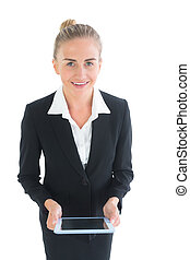 Front view of cheerful young businesswoman holding her tablet