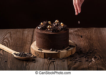 front view of chocolate cake, a hand leaving chocolate shavings, spoon wooden