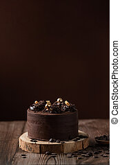 front view of chocolate cake, with chocolate chips, spoon and wooden table.