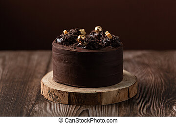 front view of chocolate cake, with chocolate chips, wooden table.